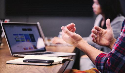 persona explicando en reunión con ordenador portátil